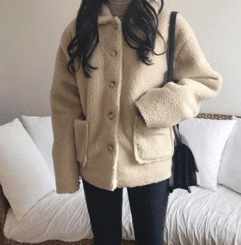 豪華な感じ暖かいラムウールのコートのポケットに見て